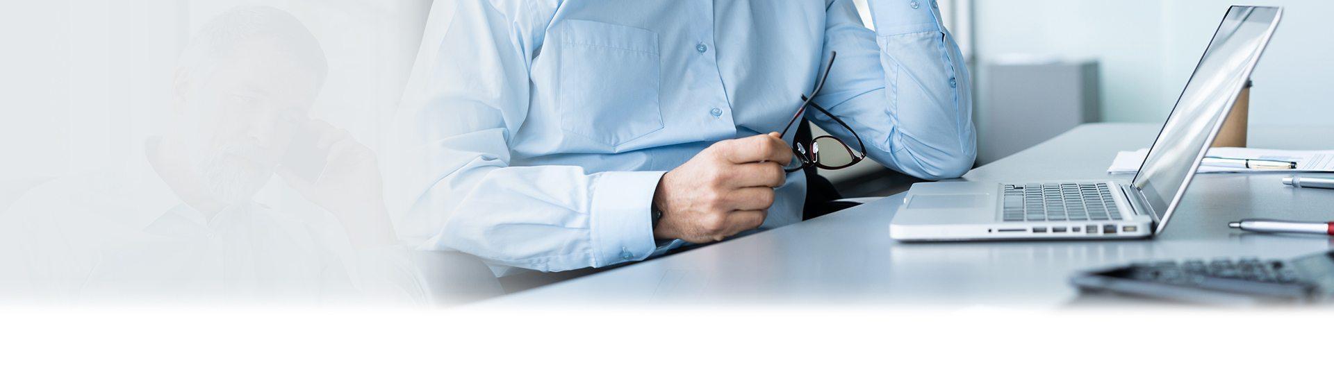 Mężczyzna przed laptopem trzymający okulary